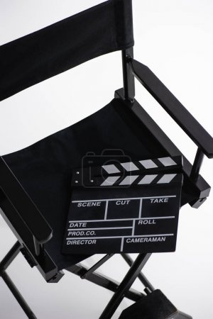 Photo for High angle view of clapperboard on director chair on white, cinema concept - Royalty Free Image