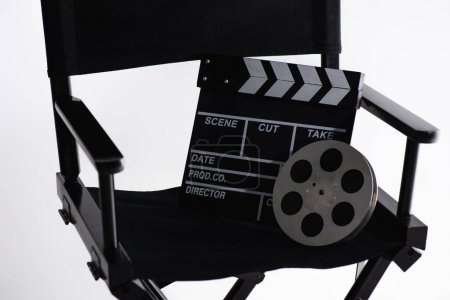Photo for Filmmaker chair, clapperboard and film bobbin on white, cinema concept - Royalty Free Image