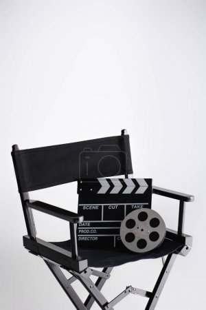 clapperboard and film reel on director chair on white with copy space, cinema concept