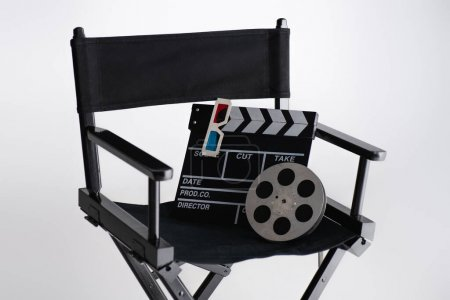 clapperboard, 3d glasses and film coil on filmmaker chair on white, cinema concept