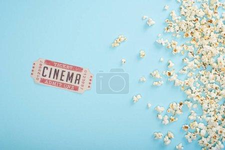 Photo pour Vue du haut du billet de cinéma près de pop-corn dispersé sur bleu - image libre de droit