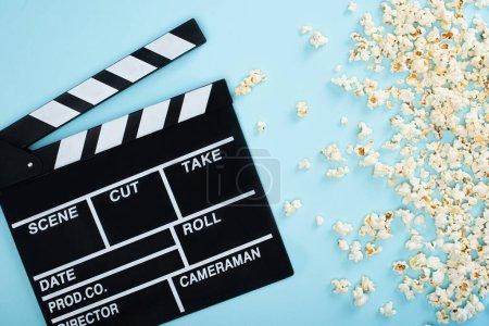 Photo pour Vue de dessus du clapperboard près du pop-corn éparpillé sur bleu, concept de cinéma - image libre de droit