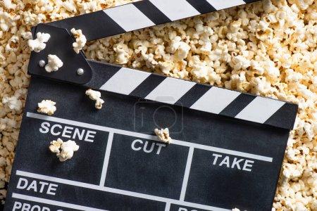 Photo pour Vue du dessus du clapperboard sur pop-corn salé, concept cinéma - image libre de droit