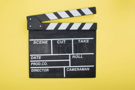 Photo for Top view of clapperboard on yellow, cinema concept - Royalty Free Image