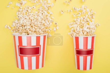Photo pour Vue de dessus des grands et petits seaux avec du pop-corn savoureux sur jaune, concept cinéma - image libre de droit