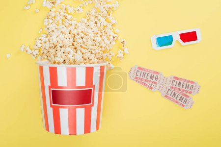 top view of bucket with popcorn, 3d glasses and cinema tickets on yellow