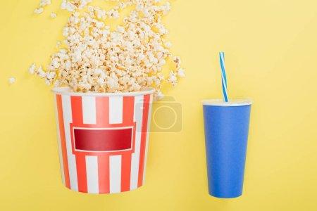 Photo pour Seau de pop-corn près de tasse de soda sur jaune, concept de cinéma - image libre de droit