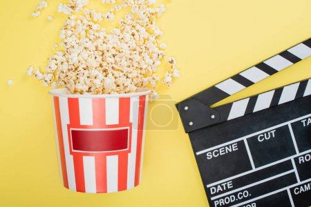 Photo for Top view of bucket with tasty popcorn near clapperboard on yellow, cinema concept - Royalty Free Image