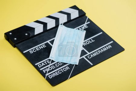 Photo for Medical mask on clapperboard on yellow, cinema concept - Royalty Free Image