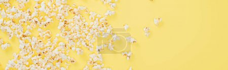 Photo for Top view of salty tasty popcorn on yellow, banner, cinema concept - Royalty Free Image