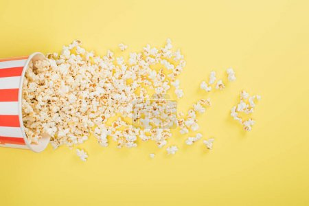 Photo for Top view of paper bucket and scattered popcorn on yellow, cinema concept - Royalty Free Image