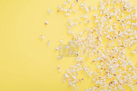 Blick von oben auf knuspriges Popcorn auf gelbem, Kinokonzept