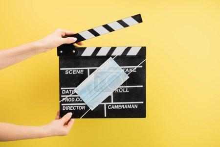 Ausgeschnittene Ansicht des Kameraassistenten mit Klappbrett und medizinischer Maske isoliert auf gelb, Kinokonzept
