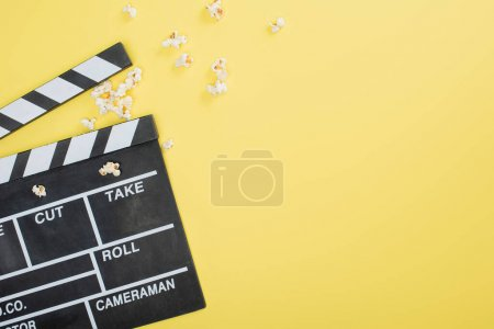 Photo for Top view of clapperboard near scattered popcorn on yellow, cinema concept - Royalty Free Image