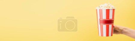 abgeschnittene Ansicht weiblicher Hand mit Popcorn-Eimer isoliert auf gelb, Banner, Kinokonzept