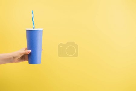 cropped view of woman holding paper cup of soda isolated on yellow, cinema concept