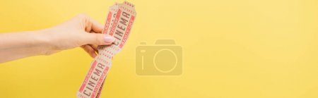 Photo for Cropped view of woman holding cinema tickets isolated on yellow, banner - Royalty Free Image