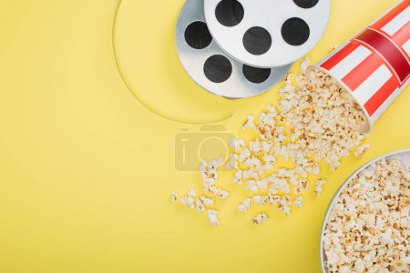 top view of film coils near buckets with popcorn on yellow, cinema concept