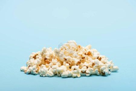 Photo pour Pile de pop-corn aérien croquant sur bleu avec espace de copie, concept de cinéma - image libre de droit