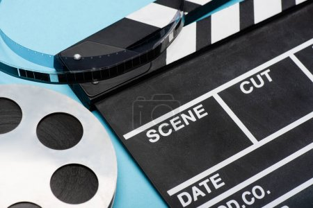 Photo for Close up view of clapperboard and film bobbin on blue, cinema concept - Royalty Free Image