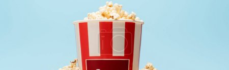Photo for Striped bucket full of crispy popcorn isolated on blue, banner, cinema concept - Royalty Free Image