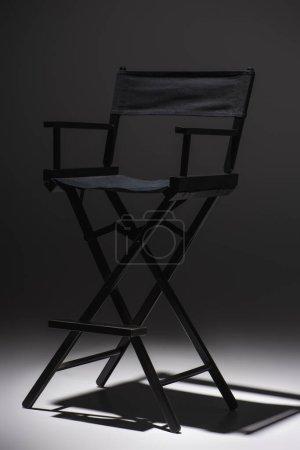 modern, black filmmaker chair on dark grey background, cinema concept