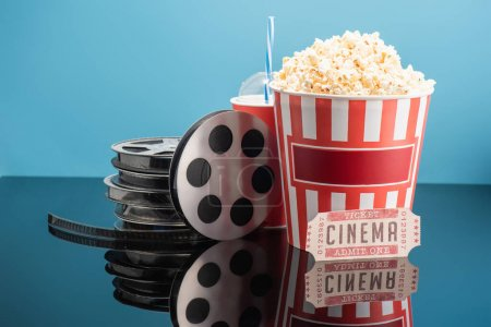 Photo for Film reels, cup of soda, cinema ticket and bucket of popcorn on glossy surface isolated on blue - Royalty Free Image