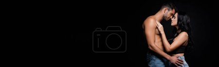 Photo for Side view of sexy couple kissing isolated on black, banner - Royalty Free Image