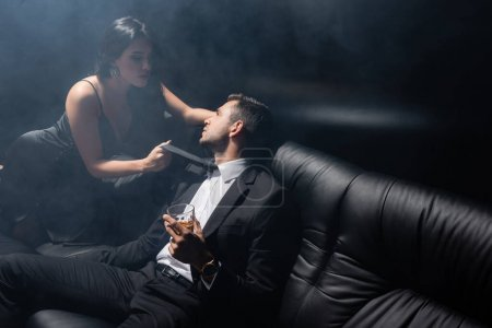 Sexy woman holding tie of boyfriend in suit holding glass of whiskey on black background with smoke