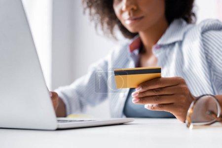 Vue recadrée de la carte de crédit en main de pigiste afro-américain à l'aide d'un ordinateur portable près des lunettes sur le premier plan flou