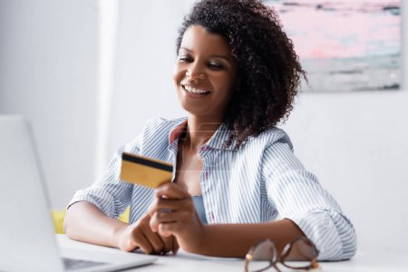 Smiling african american woman holding credit card near laptop and eyeglasses on blurred foreground
