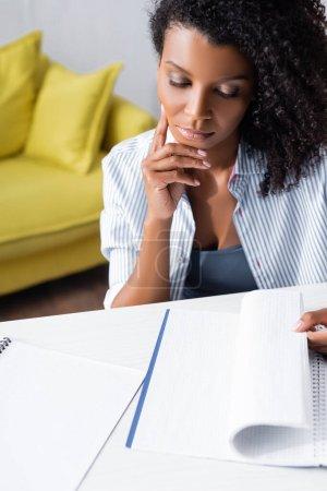 Photo pour Femme afro-américaine regardant un carnet à table - image libre de droit