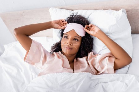 Top view of african american woman in sleep mask and pajama lying on bed