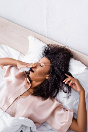 Top view of african american woman in pajamas yawning on bed