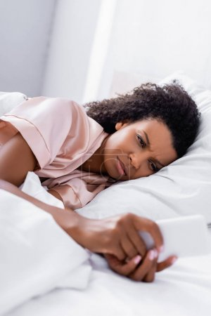 Upset african american woman using cellphone on blurred foreground on bed