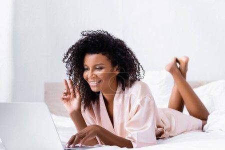Photo pour Souriante femme afro-américaine ayant un appel vidéo sur ordinateur portable au premier plan flou dans la chambre - image libre de droit