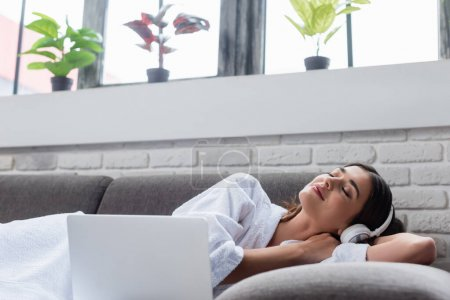 Photo for Peaceful young adult woman with closed eyes in headphones resting on couch near laptop at home - Royalty Free Image