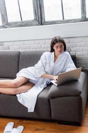 Photo for Serious young adult woman in bathrobe lying on couch and using laptop at home - Royalty Free Image