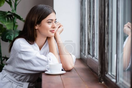 smiling young adult woman sitting with hands near face and looking out window at home