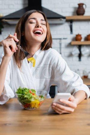 śmiejąca się młoda dorosła kobieta w szlafroku jedząca sałatkę warzywną i korzystająca z telefonu komórkowego w nowoczesnej kuchni