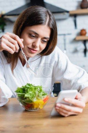 Photo pour Souriant jeune femme adulte en peignoir manger salade de légumes et regarder le téléphone portable dans la cuisine moderne - image libre de droit