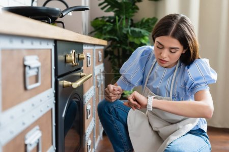 Photo for Young adult woman in apron sitting near oven and looking at wristwatch  in modern kitchen - Royalty Free Image