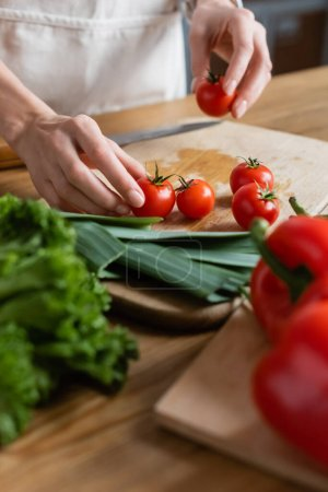 partial view of female hands holding cherry tomatoes on chopping board in modern kitchen