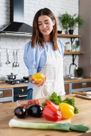 Photo for Attractive young adult woman holding yellow pepper in hand in kitchen - Royalty Free Image