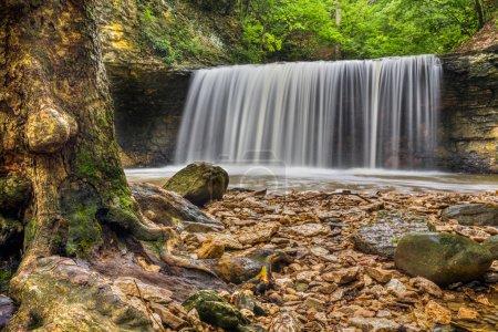 Photo pour Une belle cascade plonge sur une falaise rocheuse à Indian Run Park à Dublin, Ohio, une région qui abritait autrefois la tribu Wyandotte . - image libre de droit