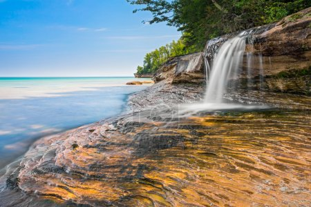 Photo for Elliot Falls is a small but beautiful waterfall that cascades over rocky ledges into Lake Superior at Pictured Rocks National Lakeshore near Munising, Michigan. - Royalty Free Image