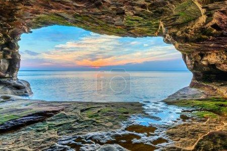 Photo pour Un magnifique coucher de soleil sur le lac Supérieur est vu depuis une grotte marine éloignée sur la côte nord de la péninsule supérieure du Michigan près de Pictured Rocks National Lakeshore . - image libre de droit