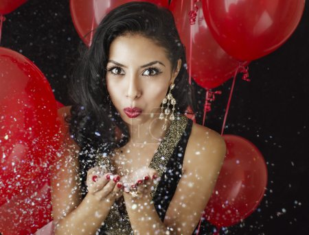 Beautiful young woman blowing confetti - red balloons background