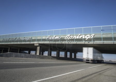 Sign for Palm Springs on I10 Highway as truck passes under bridge
