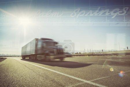 Photo pour California desert trucking double exposition image - Camion sur l'autoroute i10 en passant par Palm Springs Mohave désert zone soleil flamboyant vers le bas sur route asphaltée . - image libre de droit